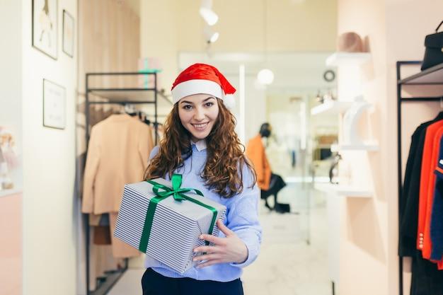 Vendeuse offre un cadeau de noël à un magasin de vêtements en vêtements de noël