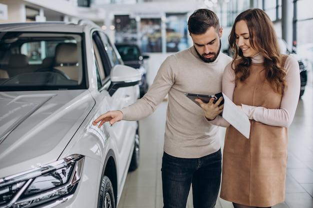 Vendeuse parlant au client dans un salon de voiture