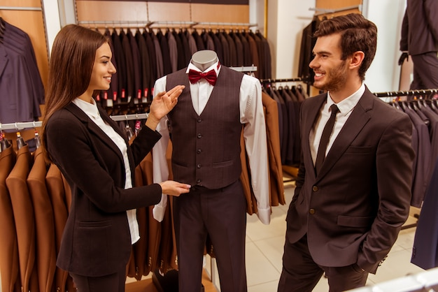 Vendeuse souriant et offrant un costume.