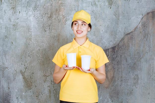 Une vendeuse en uniforme jaune tenant deux gobelets en plastique de boisson