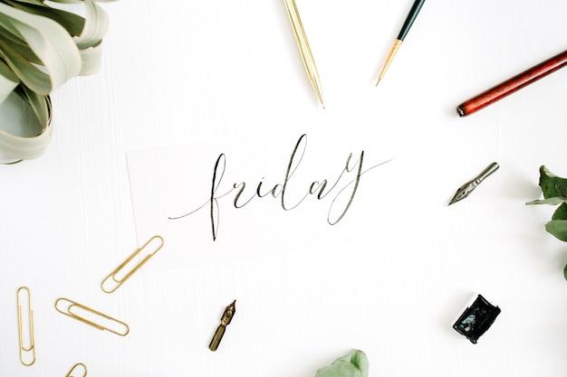 Vendredi mot écrit avec calligraphie sur blanc avec stylo, pinceau, eucalyptus et clips