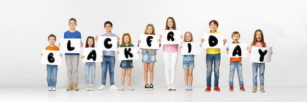 Vendredi noir, concept de vente. groupe d'enfants, d'enfants et d'adolescents vêtus de vêtements lumineux avec des émotions de bonheur tenant des lettres sur fond blanc. espace négatif. image colorée pour votre annonce.