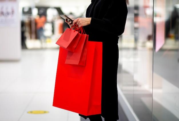 Vendredi noir, femme tenant un sac à provisions rouge sur le fond du centre commercial