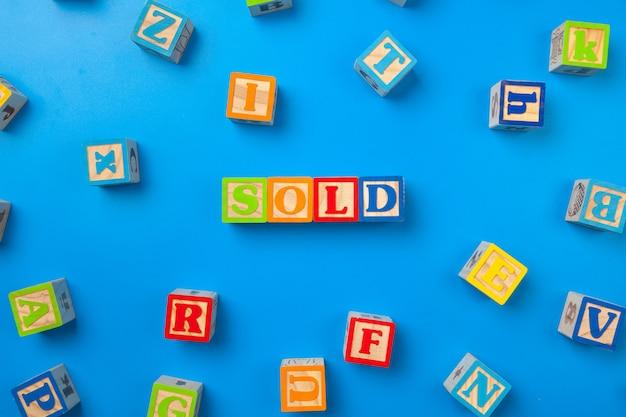 Vendu. blocs d'alphabet coloré en bois sur fond bleu, mise à plat, vue de dessus.