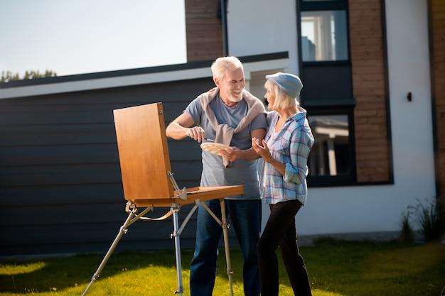 Venir au mari. femme à la retraite aux cheveux blonds portant un chapeau bleu venant à son mari dessin à l'extérieur