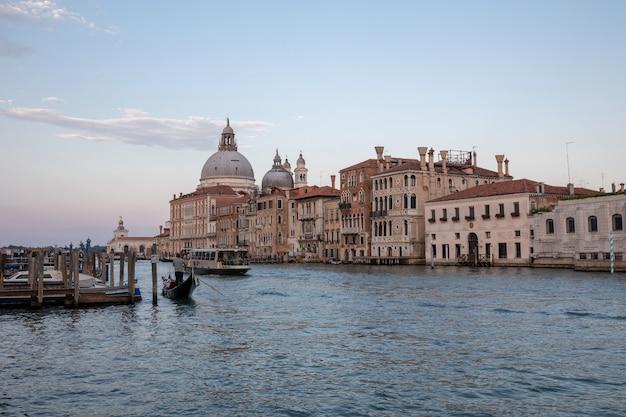 Venise, italie - 30 juin 2018 : vue panoramique sur le grand canal de venise avec bâtiments historiques, gondole et bateaux, loin de la basilique salute. paysage de jour de soirée d'été et de ciel coloré