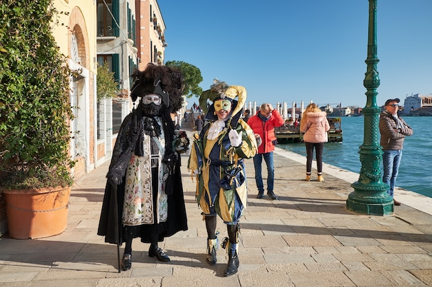 Venise italie couple en costumes et masques dans la rue pendant le carnaval