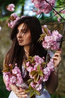 Le vent souffle les cheveux de la femme brune alors qu'elle pose devant un sakura en fleurs