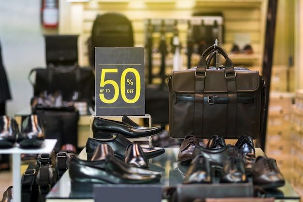 Vente 50% de réduction mock up publicité cadre d'affichage sur l'étagère des chaussures hommes dans le shopping départ