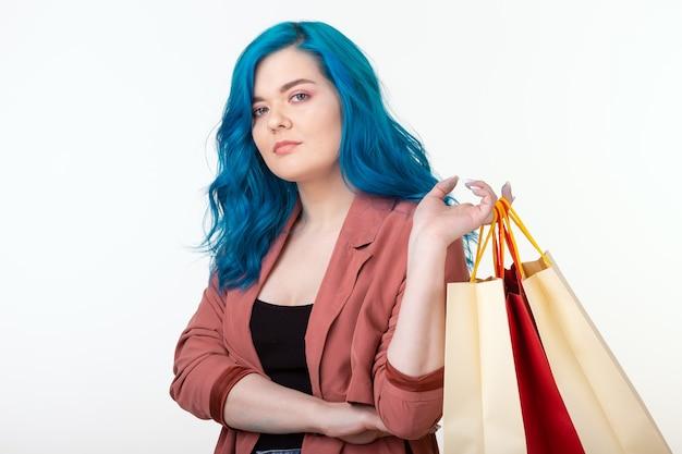 Vente, accro du shopping et concept de consommateur - belle fille aux cheveux bleus debout avec des sacs à provisions sur fond blanc.