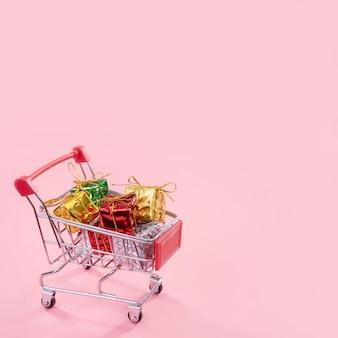 Vente annuelle, concept de saison des achats de noël. chariot de magasin mini rouge plein de boîte-cadeau isolé sur fond rose pâle