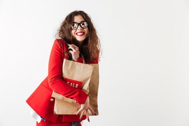 Vente attrayante femme tenant des sacs en papier isolé sur blanc