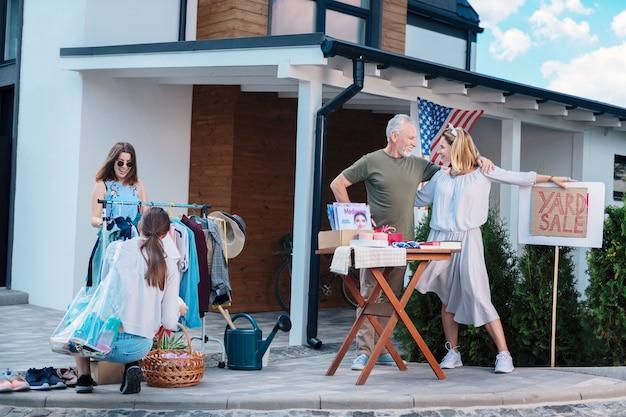 Vente de cour. agréable couple d'âge mûr se sentant extrêmement heureux tout en organisant une vente de garage le week-end et en vendant leurs vieux vêtements