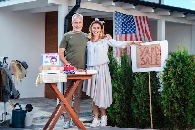 Vente dans le quartier. un couple américain généreux et généreux se sentant heureux après avoir organisé une vente de garage dans le quartier
