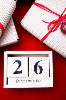 Vente du lendemain de noël. calendrier avec date sur rouge. noël . 26 décembre. boule de noël et cadeaux. vue de dessus. copyspace.