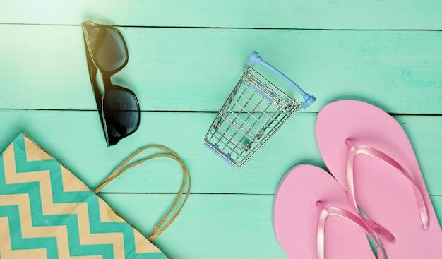 Vente d'été. notion de magasinage. accessoires de plage d'été (tongs, lunettes de soleil), mini caddie sur fond bleu en bois. vue de dessus. mise à plat