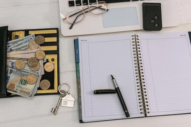 Vente ou location de clés de maison concept avec billets d'un dollar et ordinateur portable, économie