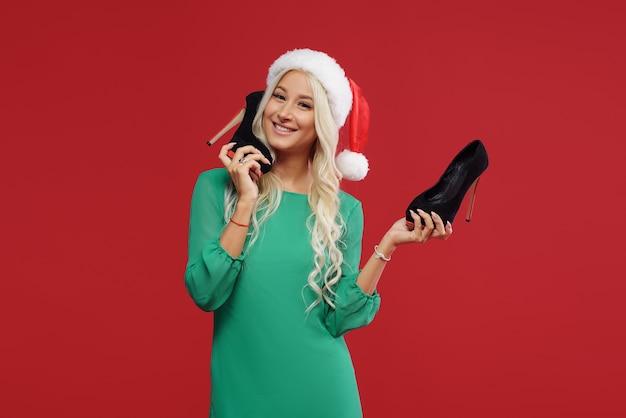 Vente de noël. heureuse jeune femme en bonnet de noel, robe verte tenant des chaussures noires sur mur rouge