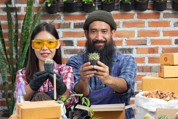 Vente de plantes en ligne; vendeurs souriants et tenant un pot de plante dans leurs mains