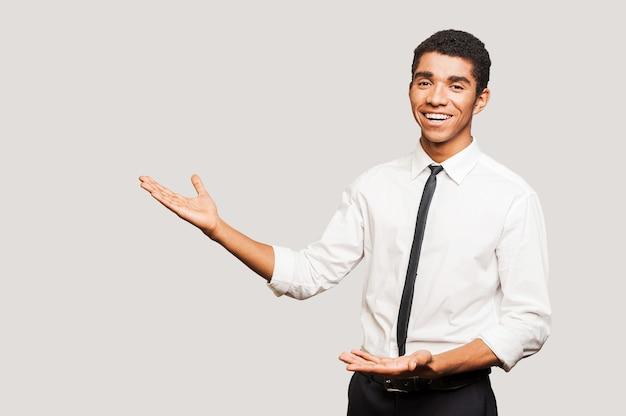 Vente positive. confiant jeune homme afro-américain en chemise regardant la caméra et pointant du doigt