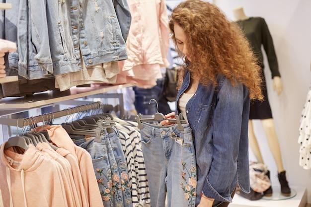 Vente de printemps de vêtements pour jeunes qui conviennent à tout adolescent élégant qui suit la mode. jeune fille choisit un jean avec broderie