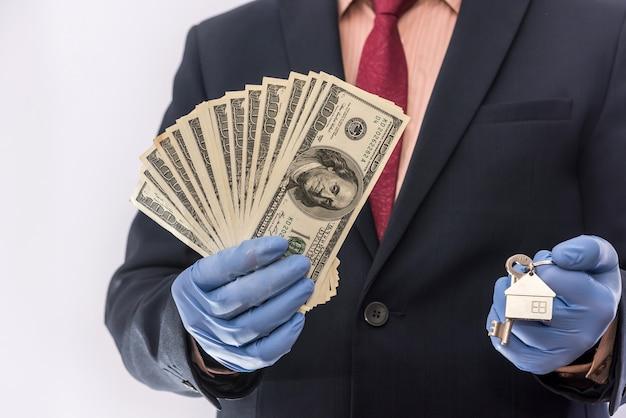 Vente de sécurité ou location d'un homme dans des gants médicaux détiennent la clé de la maison et le dollar. ncov-2019