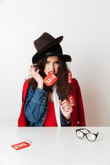 Vente sérieuse shopping femme portant des signes de vente