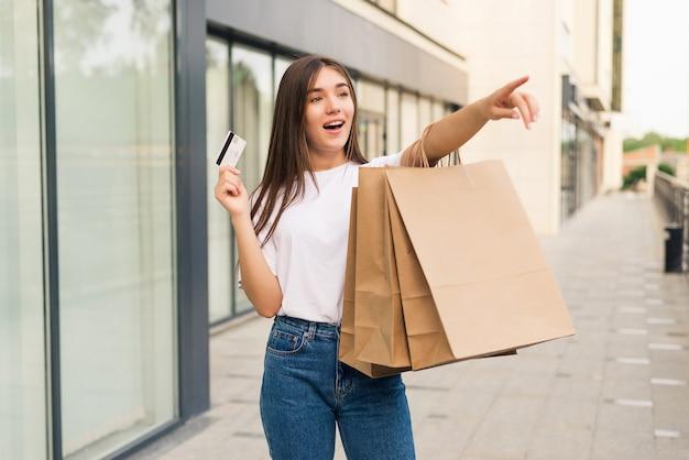 Vente, shopping, tourisme et concept de gens heureux - belle femme avec des sacs à provisions et carte de crédit dans les mains dans une rue