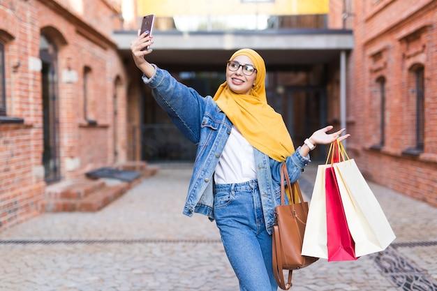 Vente, technologies et concept d'achat - heureuse femme musulmane arabe prenant selfie à l'extérieur après
