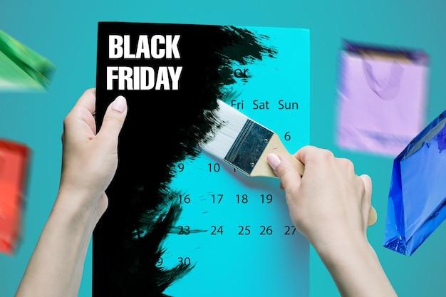 Vente de vendredi noir - concept de magasinage de vacances - texte sur carnet sur fond noir. les mains féminines tenant un pinceau