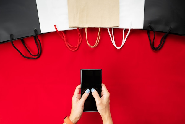 Vente de vendredi noir, main de femme achats en ligne sur smartphone avec sac à provisions sur rouge