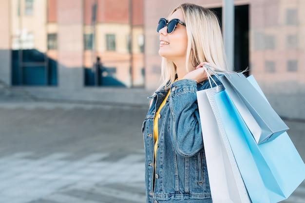 Vente vendredi noir souriante jeune femme blonde avec des sacs en papier