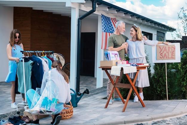 Vente de visite. deux jeunes femmes aux cheveux noirs regardant différents vêtements et chaussures venant à leurs voisins lors d'une visite de vente de garage
