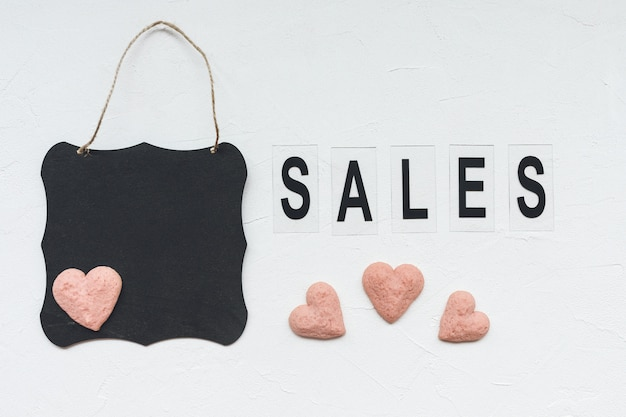 Ventes de mot, tableau noir et biscuits en forme de coeur sur blanc