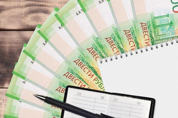 Ventilateur de billets de 200 roubles russes et bloc-notes avec carnet de contacts et stylo noir. concept de planification financière et stratégie d'entreprise