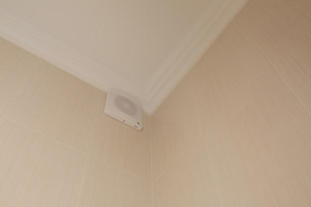 Ventilateur dans une salle de bain sur un mur beige carrelé