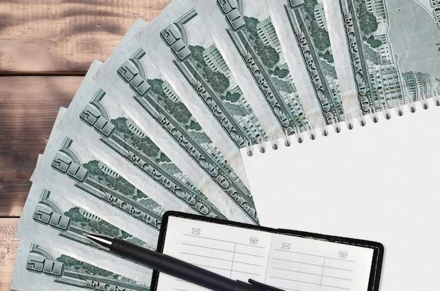 Ventilateur de factures en dollars américains et bloc-notes avec carnet de contacts et stylo noir