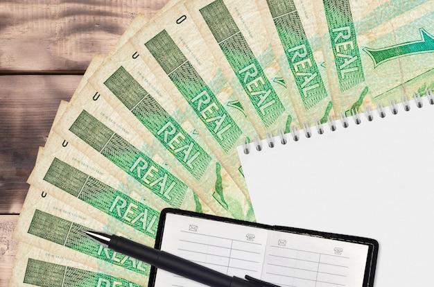 Ventilateur De Factures Réalistes Brésiliens Et Bloc-notes Avec Carnet De Contacts Et Stylo Noir Photo Premium
