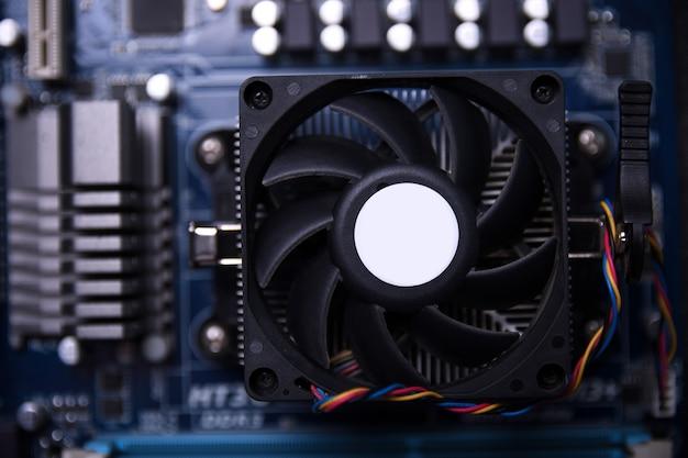 Ventilateur d'ordinateur sur la carte mère et les composants électroniques cpu cpu mémoire et différentes prises pour carte vidéo close up