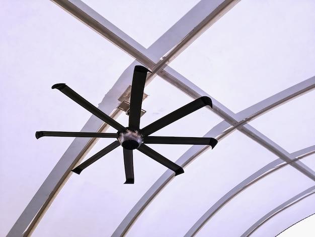 Ventilateur de plafond électrique suspendu sous une structure de toit moderne