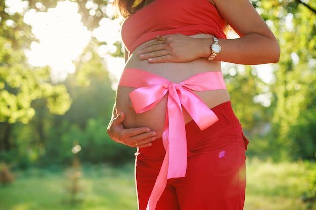 Ventre de femme enceinte attachée avec un ruban rose. portrait de femme enceinte à l'extérieur en journée ensoleillée avec espace pour le texte. ventre nu de femme attendant un bébé. grossesse saine de 9 mois