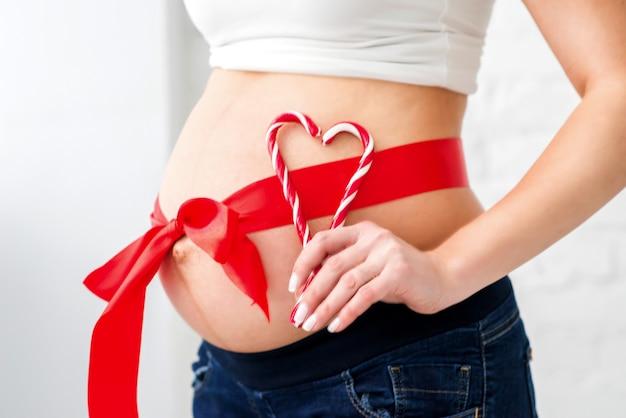 Ventre de femme enceinte avec ruban rouge et cannes de bonbon
