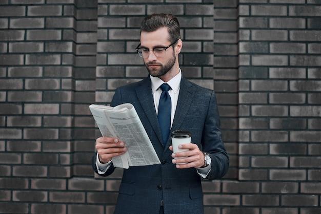 Vérification de l'actualité commerciale beau jeune homme en costume complet lire