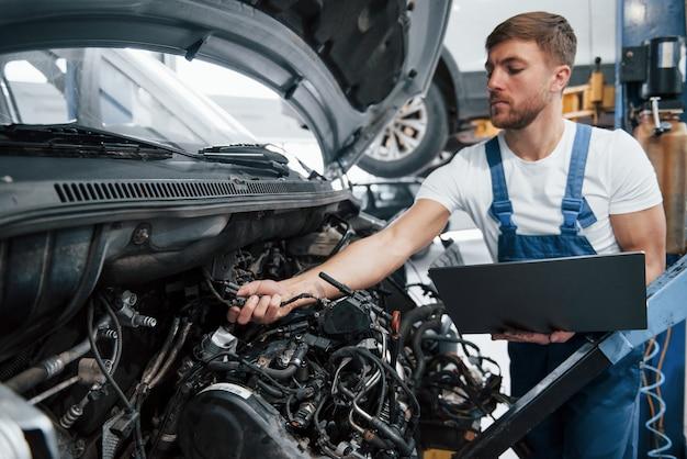 Vérification des détails. l'employé en uniforme de couleur bleue travaille dans le salon automobile.