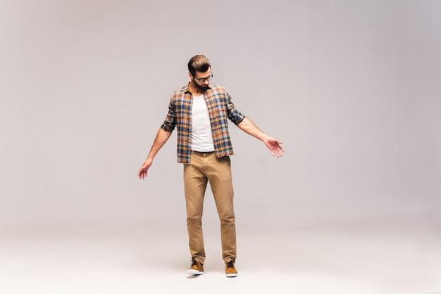 Vérification du style. prise de vue en studio sur toute la longueur d'un beau jeune homme en tenue décontractée en regardant ses vêtements