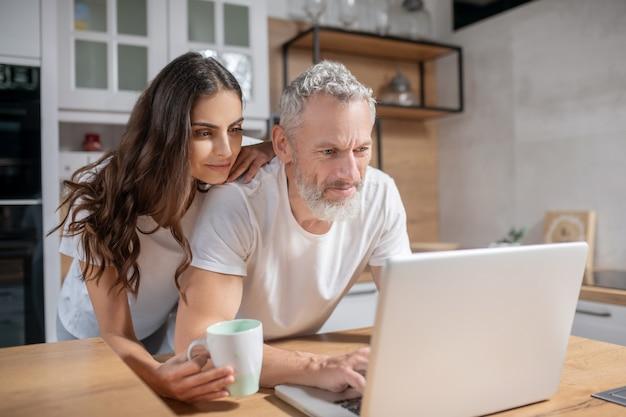 Vérification des e-mails. une femme embrassant son mari pendant qu'il vérifie ses mails