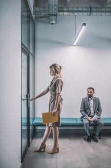 Vérification importante. jeune femme mince en robe avec des talons entrant dans le bureau et un collègue homme en costume à la recherche intéressé assis dans le couloir