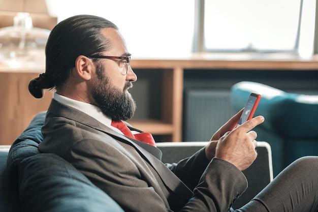 Vérification de la météo. homme barbu portant des lunettes vérifiant les prévisions météorologiques sur son téléphone