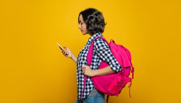 Vérification de mon emploi du temps! une jeune étudiante, habillée avec désinvolture, avec son joli sac à dos rose sur une épaule, s'est retournée pour vérifier son emploi du temps sur son téléphone.