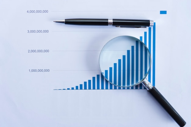 Vérification des rapports financiers. graphiques et graphiques. documents et loupe sur fond de réflexion grise.